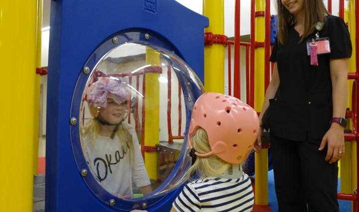 Madonna's therapy team observes Miley and McKinley playing in the indoor playground. The girls were pretending to operate a fast food restaurant.
