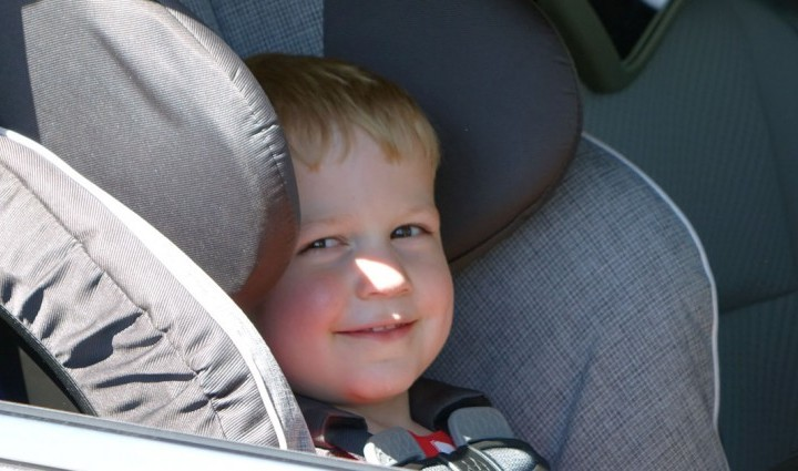 Logan, 3, smiles after being fastened into his car seat.
